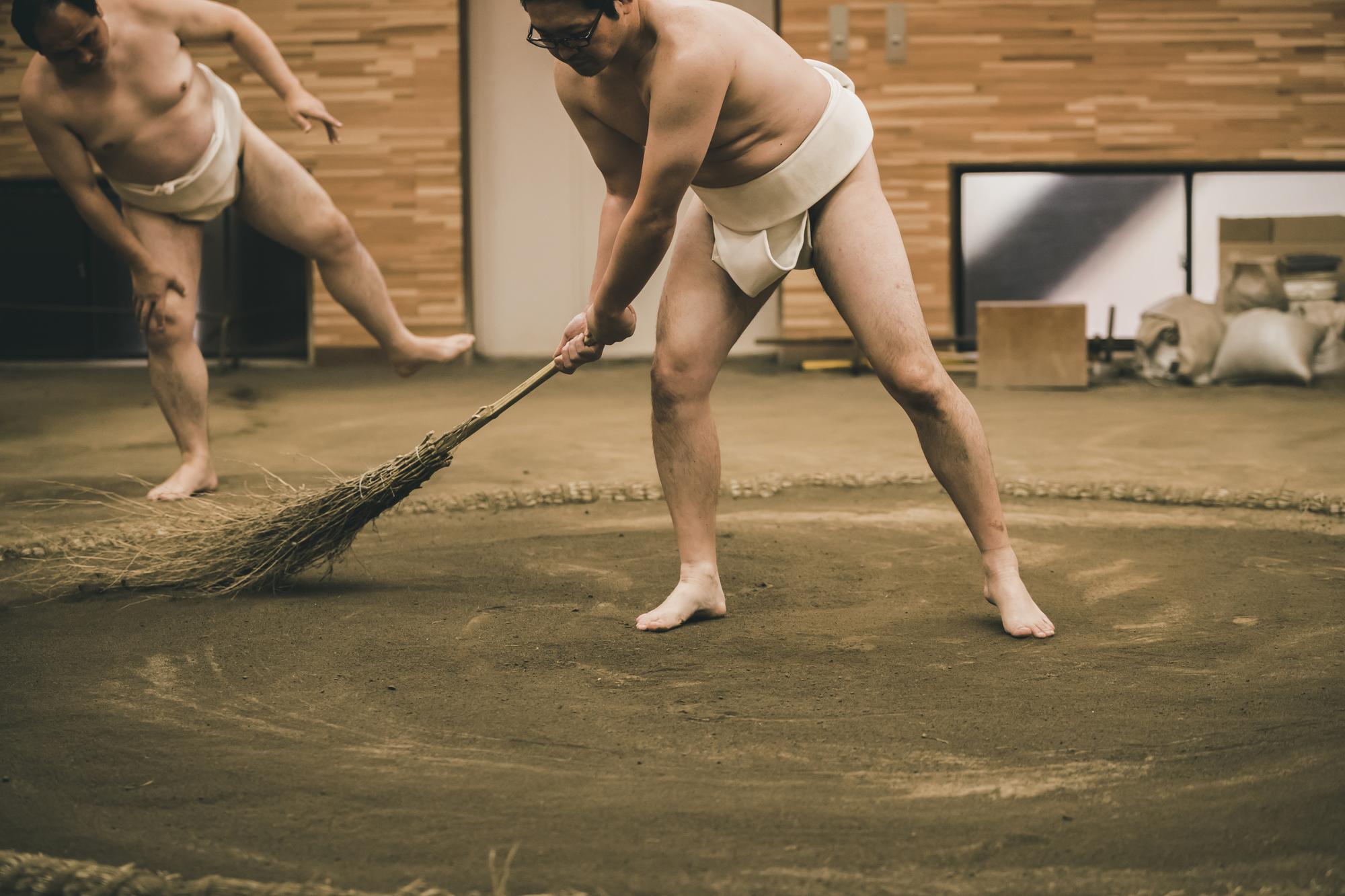 A sumo wrestler sweeping in a sumo beya