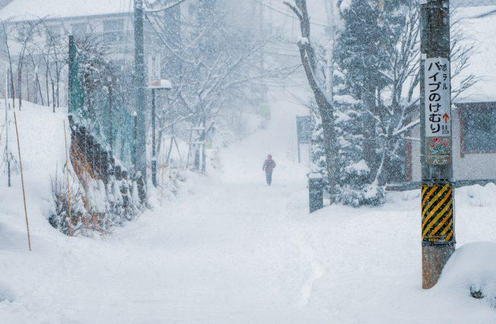 Lone person walking on a snowed street in Hakuba