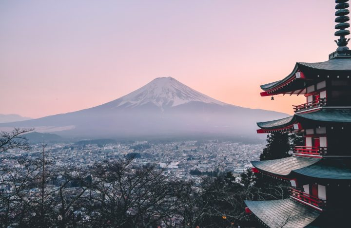 Sunset over Mount Fuji seen from a distance with city in the foreground