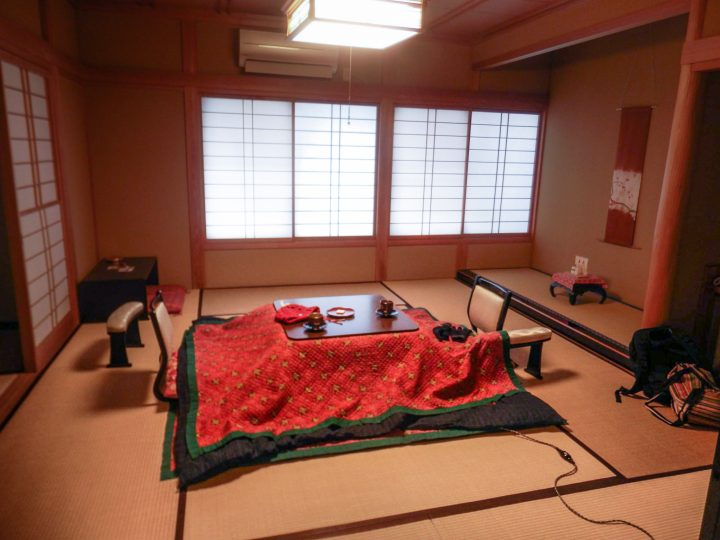 Traditional Japanese room with low chairs, tatami mats and a kotatsu
