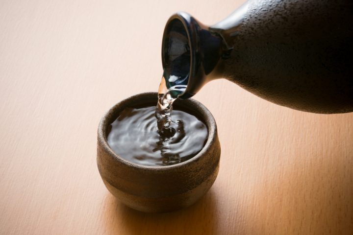 Close up of sake being poured on a ceramic cup