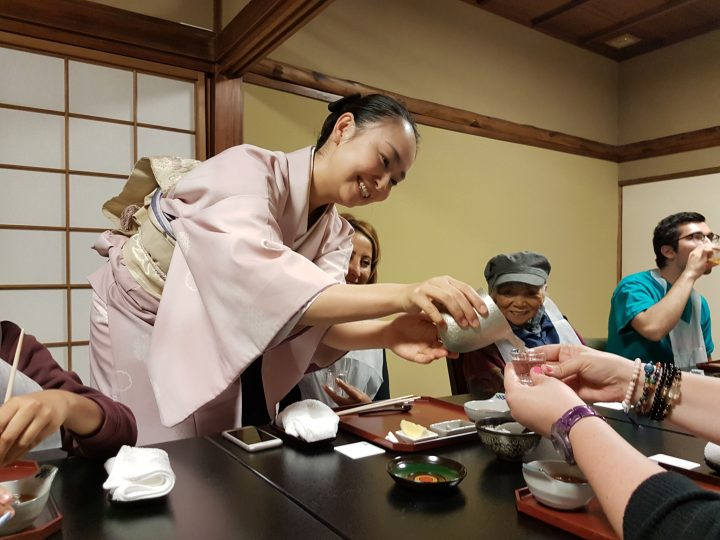Smiling waitress wearing traditional clothes serves sake to a group of customers in a Kyoto restaurant