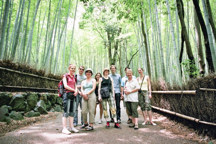 A group of travelers smile while standing in the middle of the bamboo forest in Arashiyama