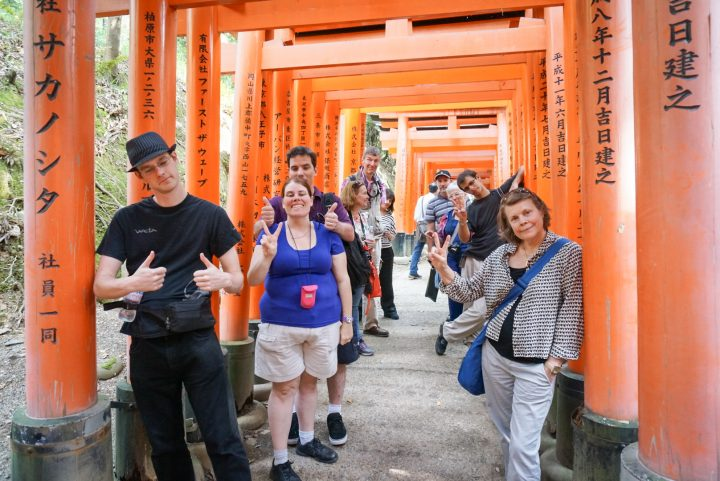 Group of smiling travelers pose for a photo among the red gates of Fushimi Inari shrine, in Kyoto