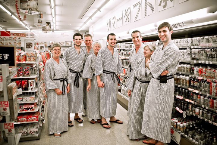 A group of westerners dressed in yukatas smile at a combini store