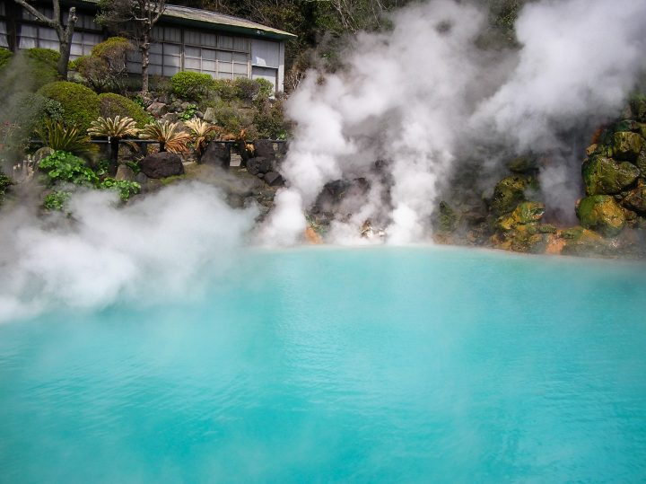 Colourful water in hot spring with smoke and vapor coming out