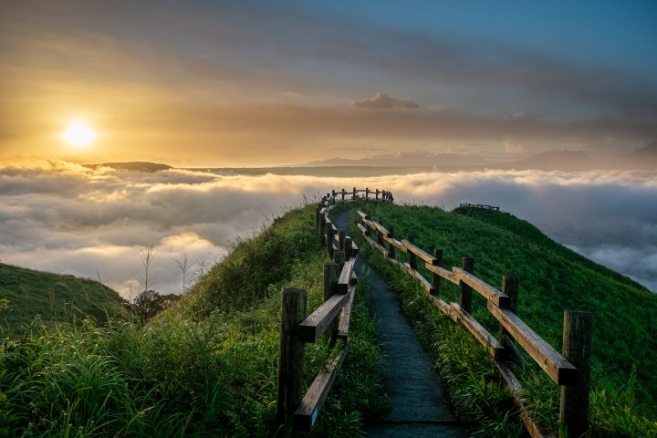 Wooden walkway on green mountain with clouds and sun in the background