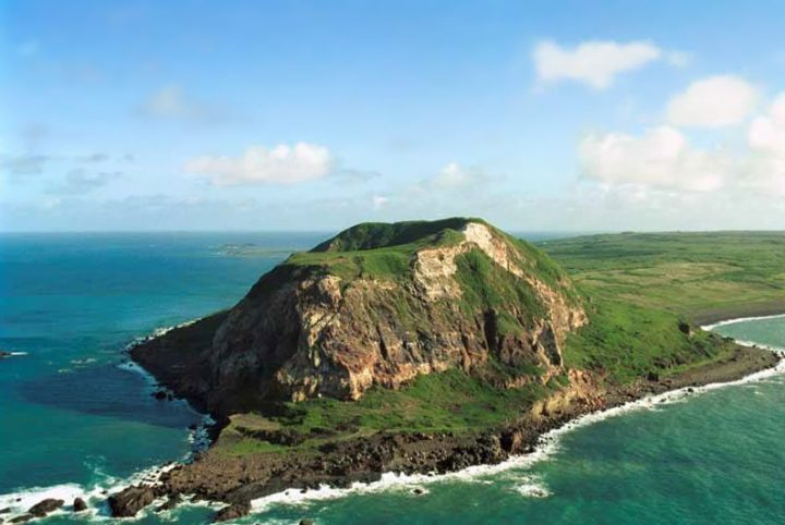 Aerial shot of the island of Iwo Jima covered in green grass