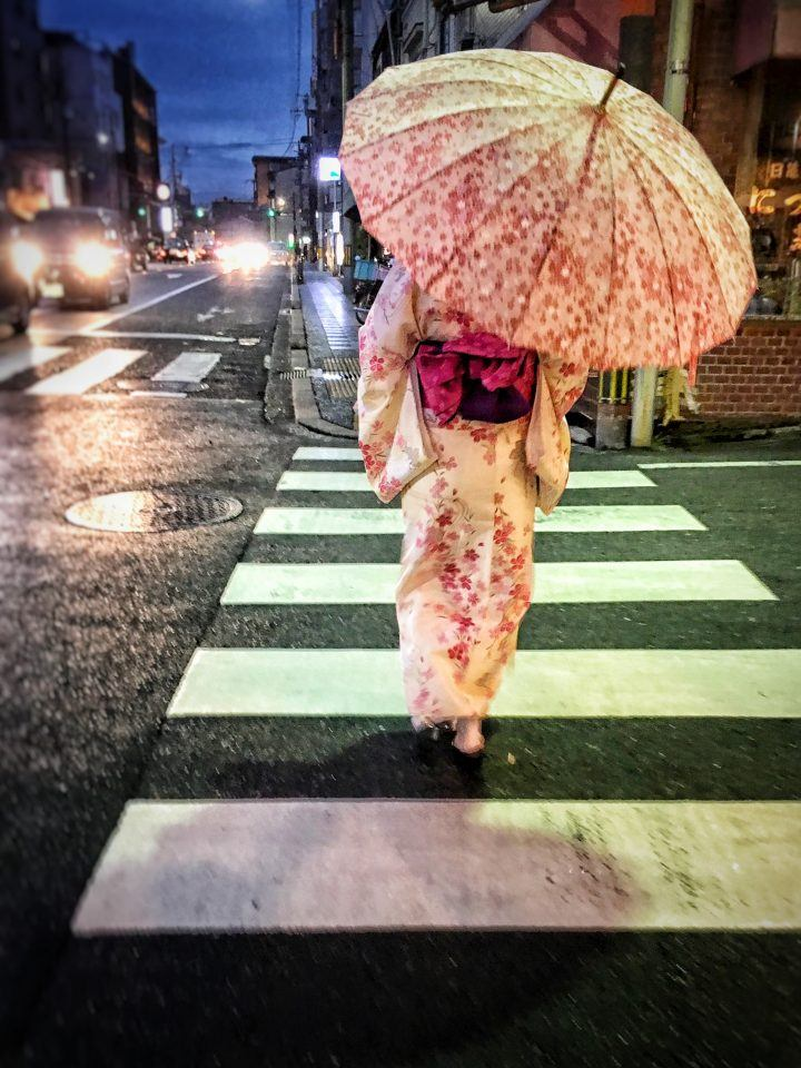 Lady in kimono with umbrella crosses a road in Kyoto