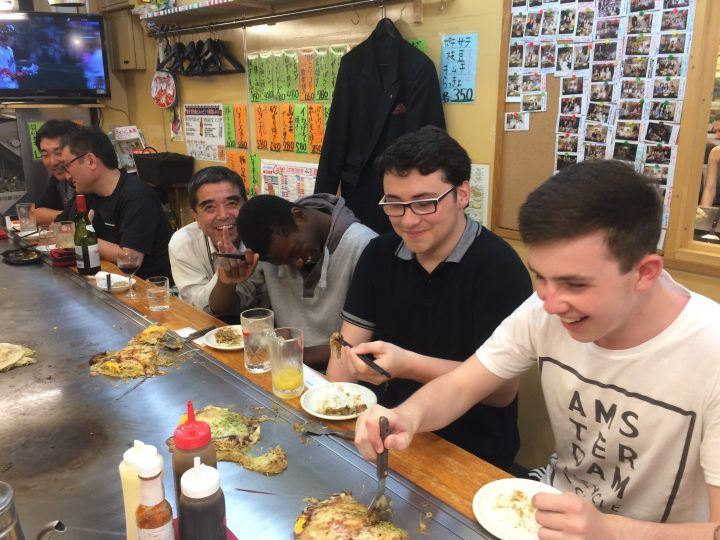 Teenagers trying okonomiyaki in Japan