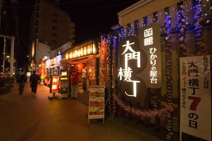 Elegant night lights from restaurants in city promenade
