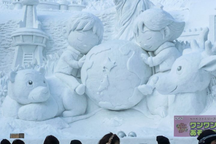 Ice sculpture of children sitting on animals and hugging planet earth during Sapporo Snow Festival