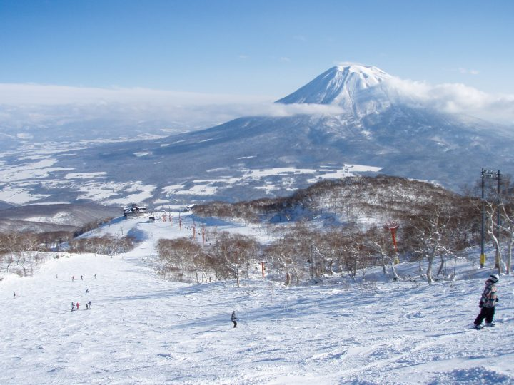 Skiers on snowy slopes with ice-capped mountain in the background