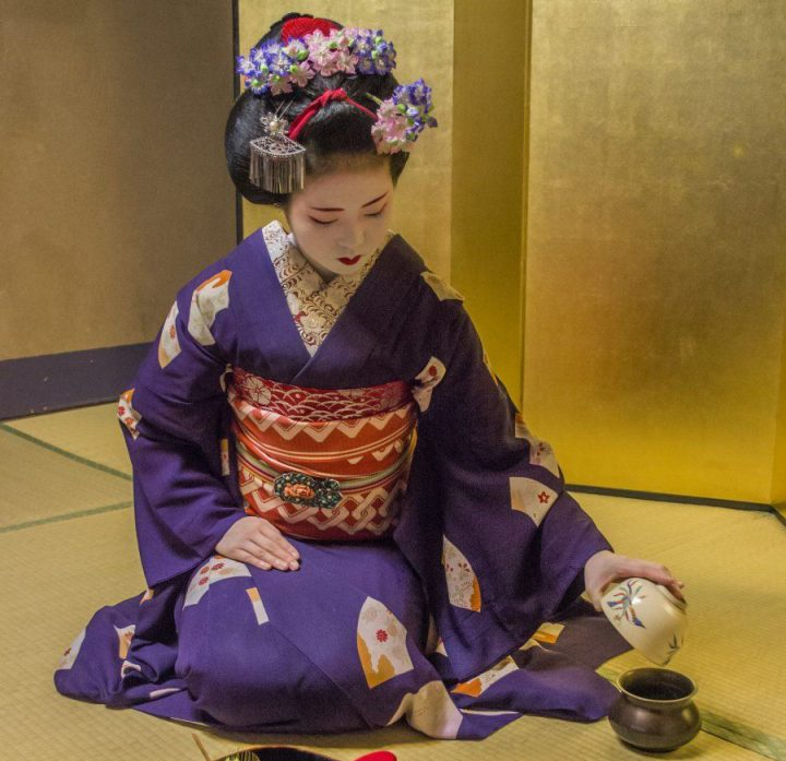 Apprentice geisha dressed in purple pours tea in cup while kneeling on tatami mats