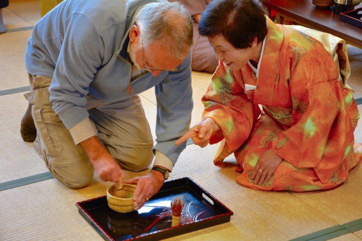 Instructor dressed in kimono teaches western tourist how to prepare green tea