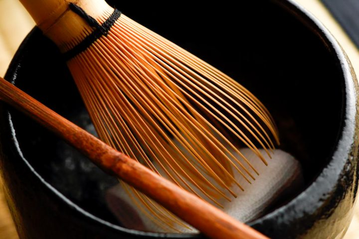 Close-up of green tea bamboo whisk inside a ceramic cup