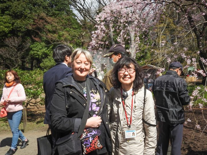 Smiling traveler with her Japanese guide in front of cherry blossoms