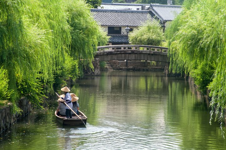 Boat gently wades in canal surrounded by trees