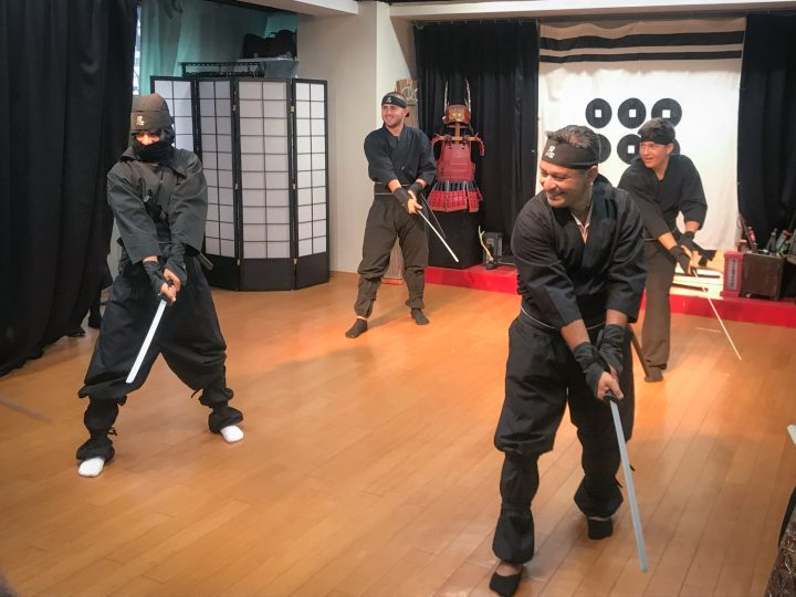 Four men dressed in black holding traditional Japanese swords