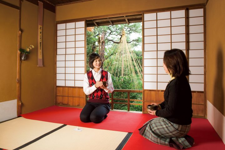 Two women kneeling on the ground in a tatami room while having tea