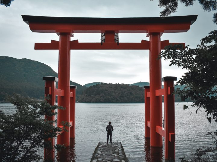 Lone person standing on the traditional gate of Hakone Shrine