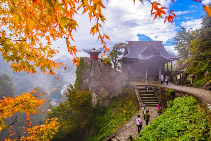 Autumn colours on mountain temple with hikers on its paths
