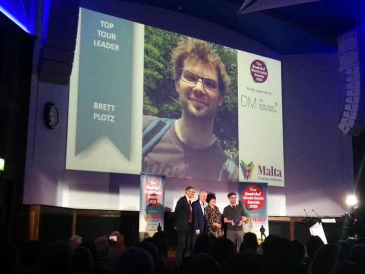 Tour leader Brett Plotz  on stage receiving his award for world excellence