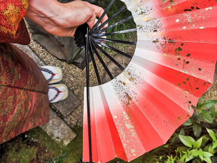 Hand holding bright red fan with specs of gold