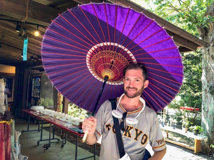 Man holding a traditional purple Japanese umbrella