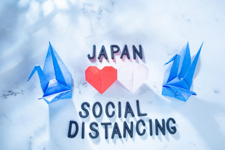 "Stock photo of two paper cranes, with the words ""Japan Social Distancing"" and two hearts between them"