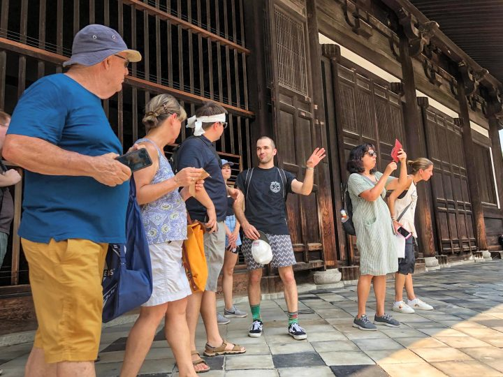 Tour leader talking to travelers in front of a temple