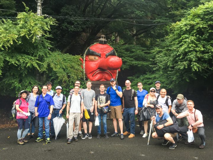 A crowd of InsideJapan Tours employees in front of a red Tengu statue