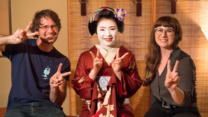 Two smiling travelers with an apprentice geisha