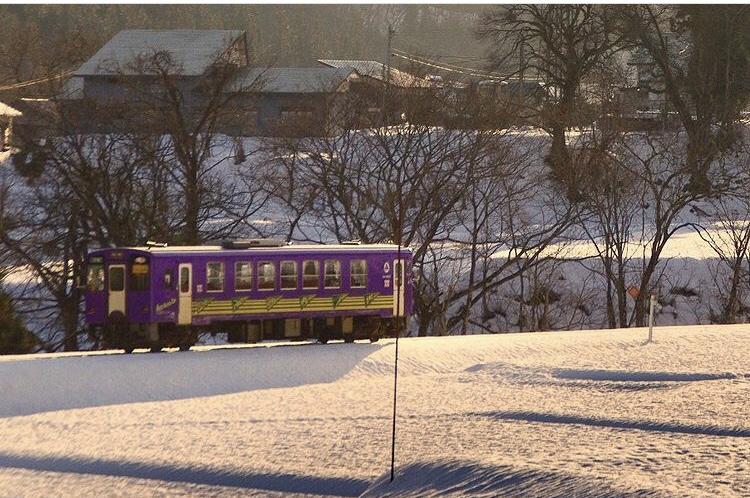 A small purple train glides over a snowy landscape in wintry Niigata