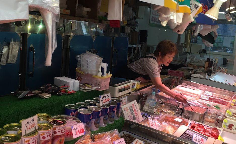 Woman leans over fresh fish below neon lights at Furukawa Fish Market, Aomori