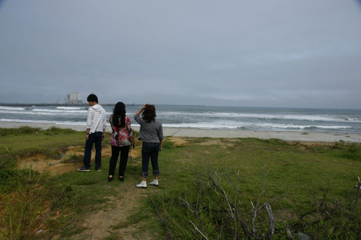 Three people stand on grass while looking at the ocean after the tsunami