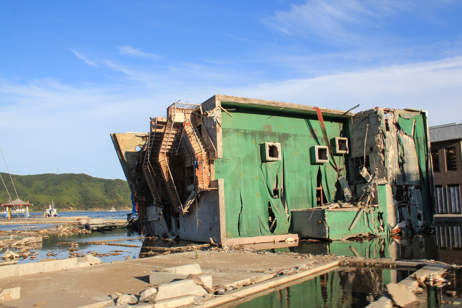 Building with green roof lies on its side in Onagawa after the tsunami of 2011