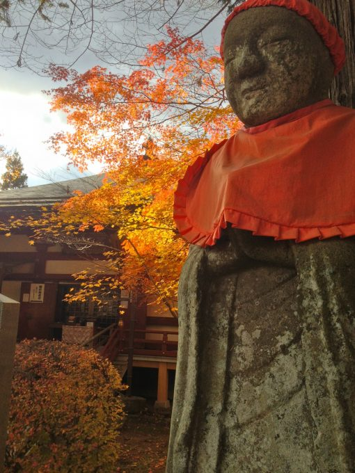 Stone statue wearing cloth bib and cap at Chusonji, Hiraizumi, with red autumn leaves in the background