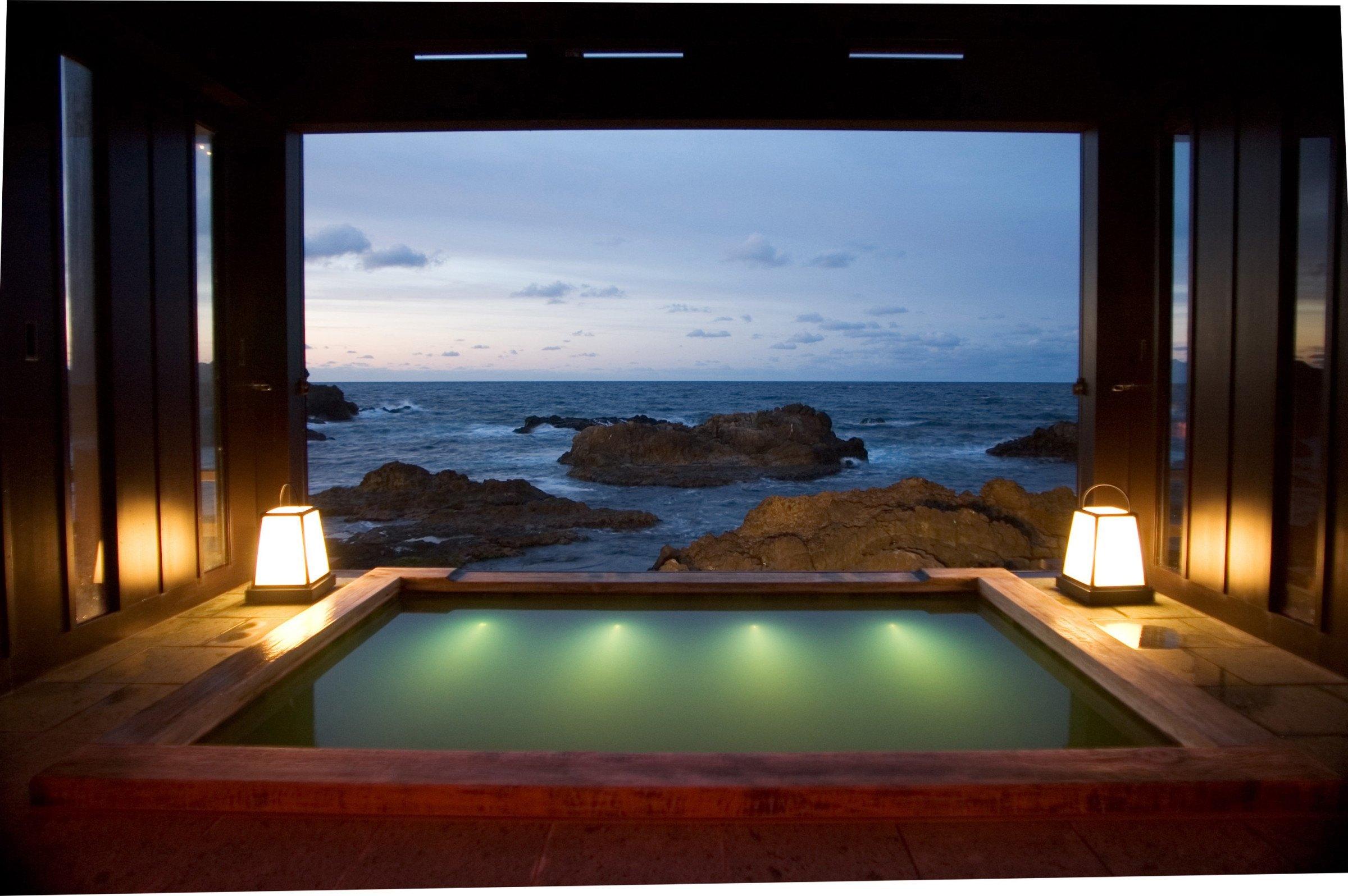 A hot spring bath overlooking the ocean at Lamp no Yado